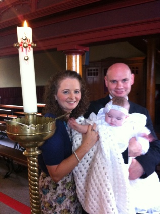 Katie Michaela Flynn on her baptism day with her parents Caitriona and Derek.