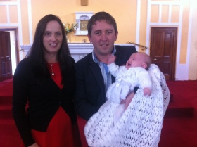 Doireann on her baptism day with her parents Deirdre and Alan.