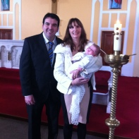 Eve Rose on her baptism day with her parents.