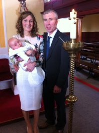Oisin on his baptism day with his parents.