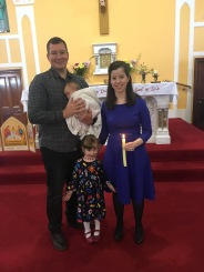 Clodagh Carmel Aylward on her baptism day with her parents Sharon and Wayne and sister, Keela.