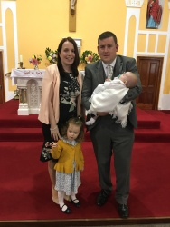 Domhnall with his parents snd sister on his baptism day.