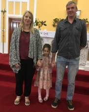 Holly Moylan with her parents on her baptism day.